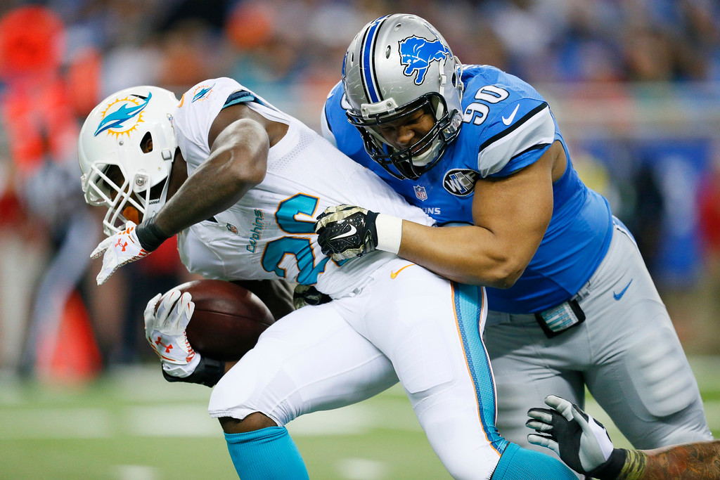. Detroit Lions defensive tackle Ndamukong Suh (90) stops Miami Dolphins running back Lamar Miller (26) during the first half of an NFL football game in Detroit, Sunday, Nov. 9, 2014. (AP Photo/Rick Osentoski)