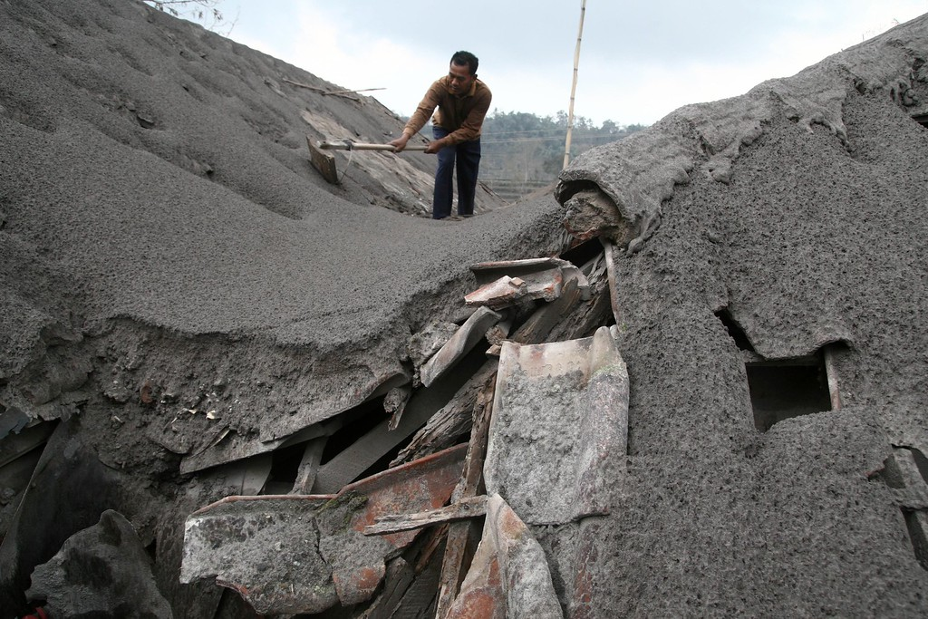 . An Indonesian resident clears a roof damaged by heavy ashfall, following the eruption of Mount Kelud on February 13, in Malang in East Java on February 16, 2014. AFP PHOTO/AMAN ROCHMAN/AFP/Getty Images