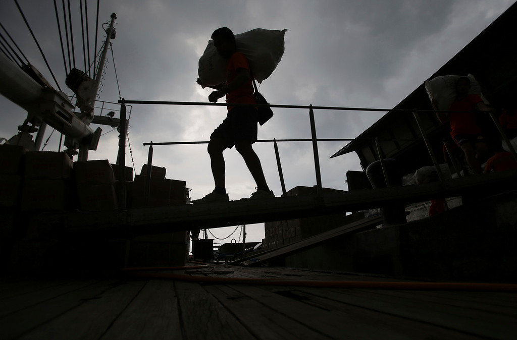 . A Philippine Coast Guard crew carries relief goods on a Coast Guard ship docked at Manila\'s pier, Philippines, before heading to earthquake-struck Cebu and Bohol provinces on Wednesday, Oct. 16, 2013.  (AP Photo/Aaron Favila)