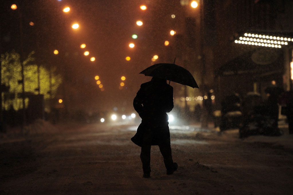 . A man walks on West 49th Street as snow falls during the rush hour January 21, 2014 in New York. In New York, a storm alert was issue for noon (1700 GMT) Tuesday to 6:00 am (1100 GMT) Wednesday with as much as a foot (30 centimeters) forecast for the metropolitan region. AFP PHOTO/Stan HONDA/AFP/Getty Images