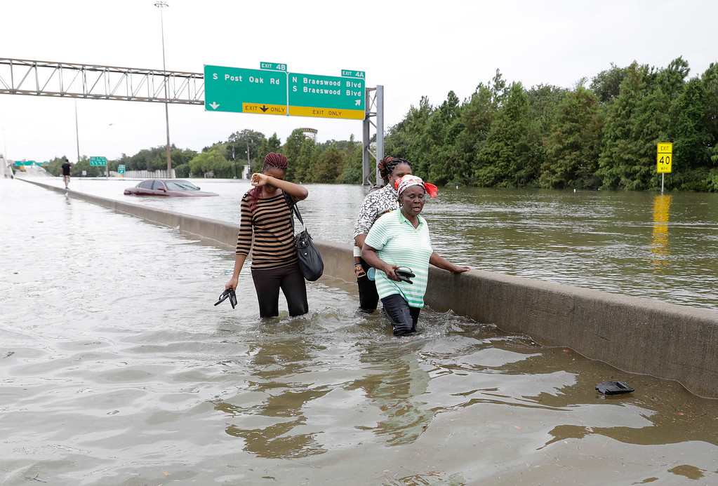 . Evacuees wade down a flooded section of Interstate 610 as floodwaters from Tropical Storm Harvey rise Sunday, Aug. 27, 2017, in Houston, Texas. (AP Photo/David J. Phillip)