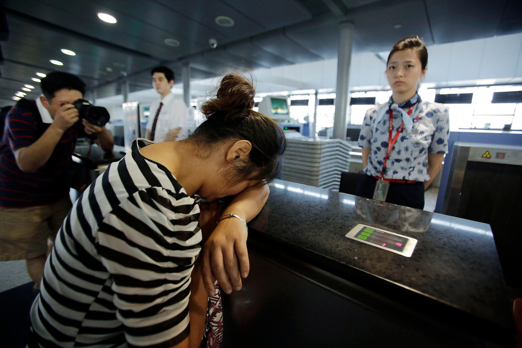 . An unidentified family member of one of two Chinese students killed in a crash of an Asiana Airlines\' plane on Saturday, cries at the airline\'s counter as she and other family members check in for a flight to San Francisco, at Pudong International Airport in Shanghai, China, Monday, July 8, 2013. The Asiana flight crashed upon landing Saturday, at San Francisco International Airport, and two of the 307 passengers aboard were killed. (AP Photo/Eugene Hoshiko)