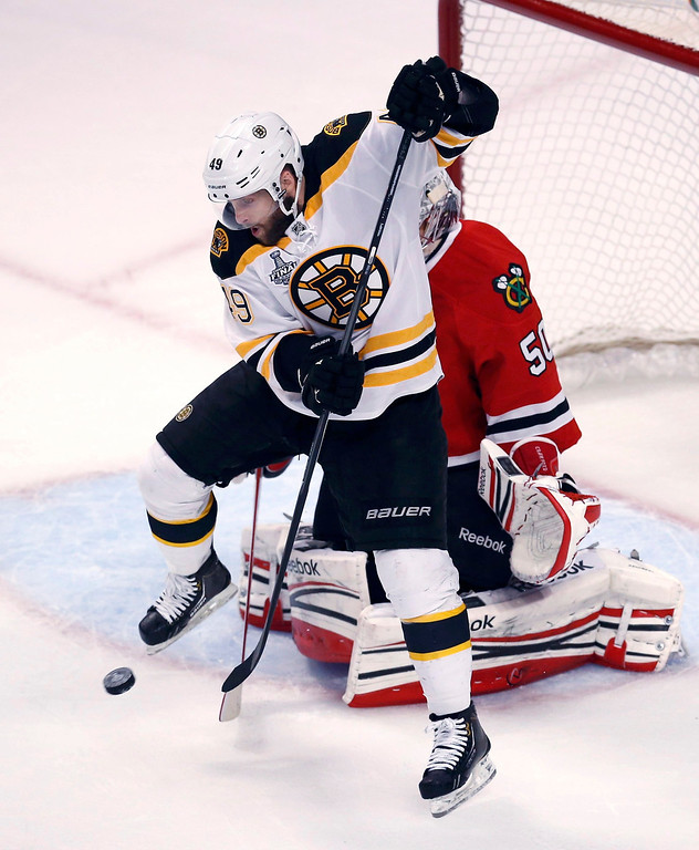 . Boston Bruins\' Rich Peverley jumps as he screens Chicago Blackhawks goalie Corey Crawford during the first period in Game 1 of their NHL Stanley Cup Finals hockey game in Chicago, Illinois, June 12, 2013. REUTERS/Jim Young