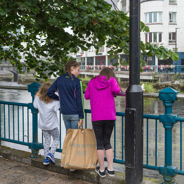 Siblings standing against the railing of riverbank, Sligo, County Sligo, Ireland