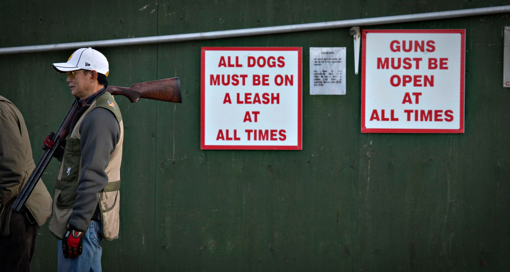 Description of . A man rests a shotgun on his shoulder next to signs posted on a wall at the Vancouver Gun Club in Richmond, British Columbia February 10, 2013. Formed in 1924, the Vancouver Gun Club, which is a shotgun-only club, has a regular membership of about 400 and sells an estimated 1100 day passes each year. Canada has very strict laws controlling the use of handguns and violent crime is relatively rare. Picture taken February 10, 2013.  REUTERS/Andy Clark