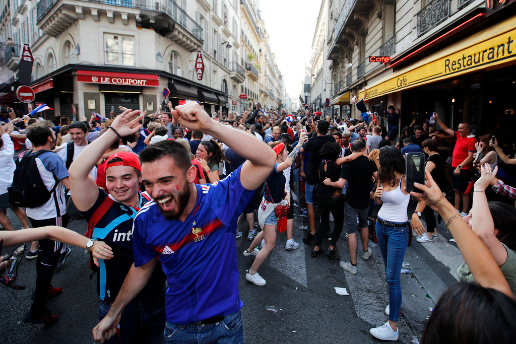 . French soccer team supporters celebrate in a street after France won the soccer World Cup final match between France and Croatia, Sunday, July 15, 2018 in Paris. France won its second World Cup title by beating Croatia 4-2 . (AP Photo/Francois Mori)