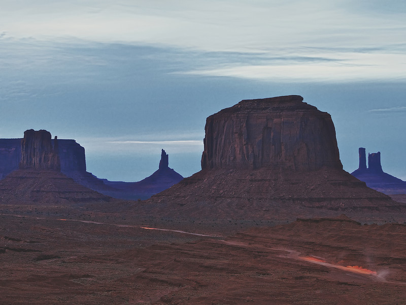 A cloud covered moon over Monument Valley
