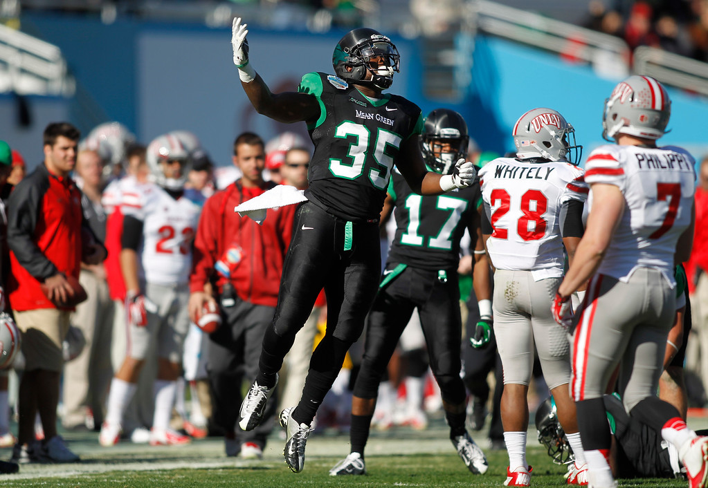 . North Texas linebacker Zach Orr (35) celebrates after North Texas recovered a punt fumbled by UNLV running back Keith Whitely (28) during the first half of the Heart of Dallas NCAA college football game, Wednesday, Jan. 1, 2014, in Dallas. (AP Photo/Mike Stone)