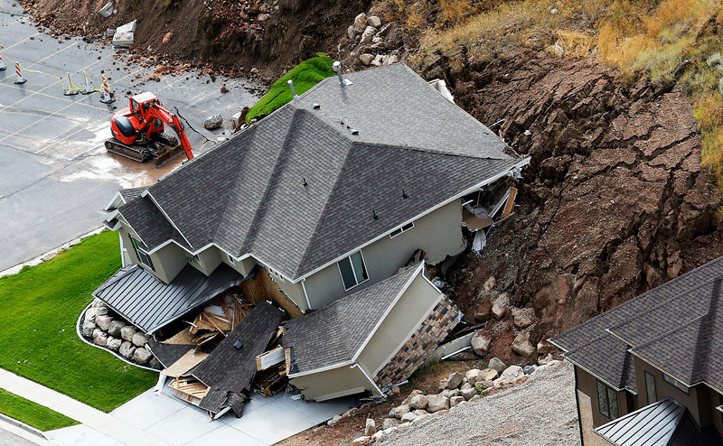 . A home is damaged by a mudslide, Tuesday, Aug. 5, 2014 in North Salt Lake, Utah.  The home crumbled after rain-saturated soil from the hill above started piling up behind it at around 6 a.m. Tuesday.   No injuries have been reported. (AP Photo/The Deseret News, Ravell Call)