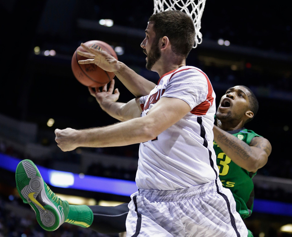 . Oregon forward Carlos Emory, right, blocks a shot by Louisville guard Luke Hancock during the first half of a regional semifinal in the NCAA college basketball tournament, Friday, March 29, 2013, in Indianapolis. (AP Photo/Michael Conroy)