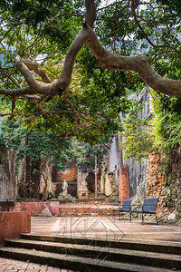 Statue in public courtyard with benches.  Brick walls in disrepair.  Grungy and in ruins