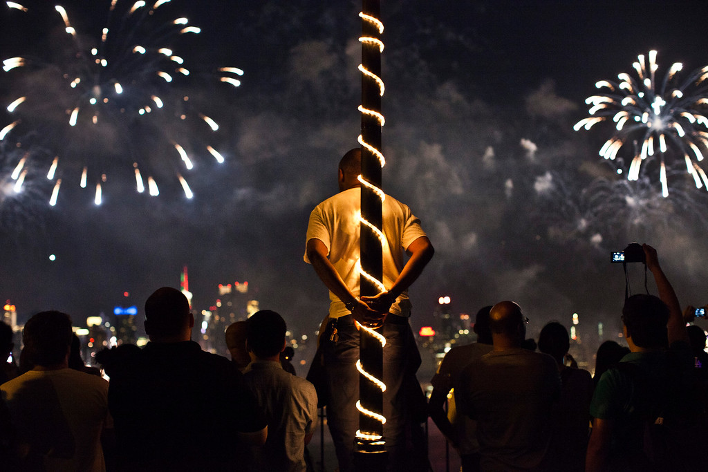. WEEHAWKEN, NJ - JULY 4: People watch fireworks light up the sky over New York City on July 4, 2013 in Weehawken, New Jersey. July 4th is a national holiday with the nation celebrating its 238th birthday.  (Photo by Kena Betancur/Getty Images)