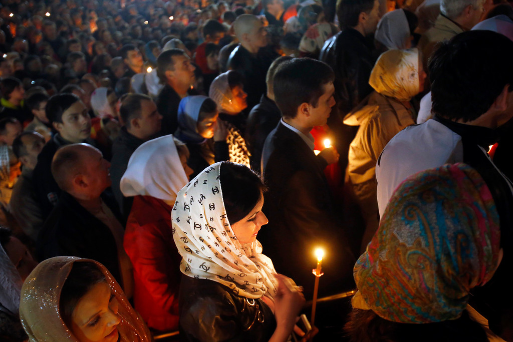 . Orthodox devotees carry candles during Easter Sunday rites in Donetsk, Ukraine, early Sunday, April 20, 2014. (AP Photo/Sergei Grits)