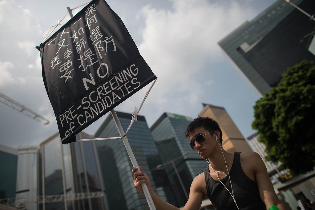 . A protester holds a banner on a street outside of Hong Kong Government Complex on October 2, 2014 in Hong Kong. Protesters have threatened to widen their campaign with a new deadline of midnight tonight, calling for open elections and the resignation of Hong Kong\'s Chief Executive Leung Chun-ying.  (Photo by Anthony Kwan/Getty Images)