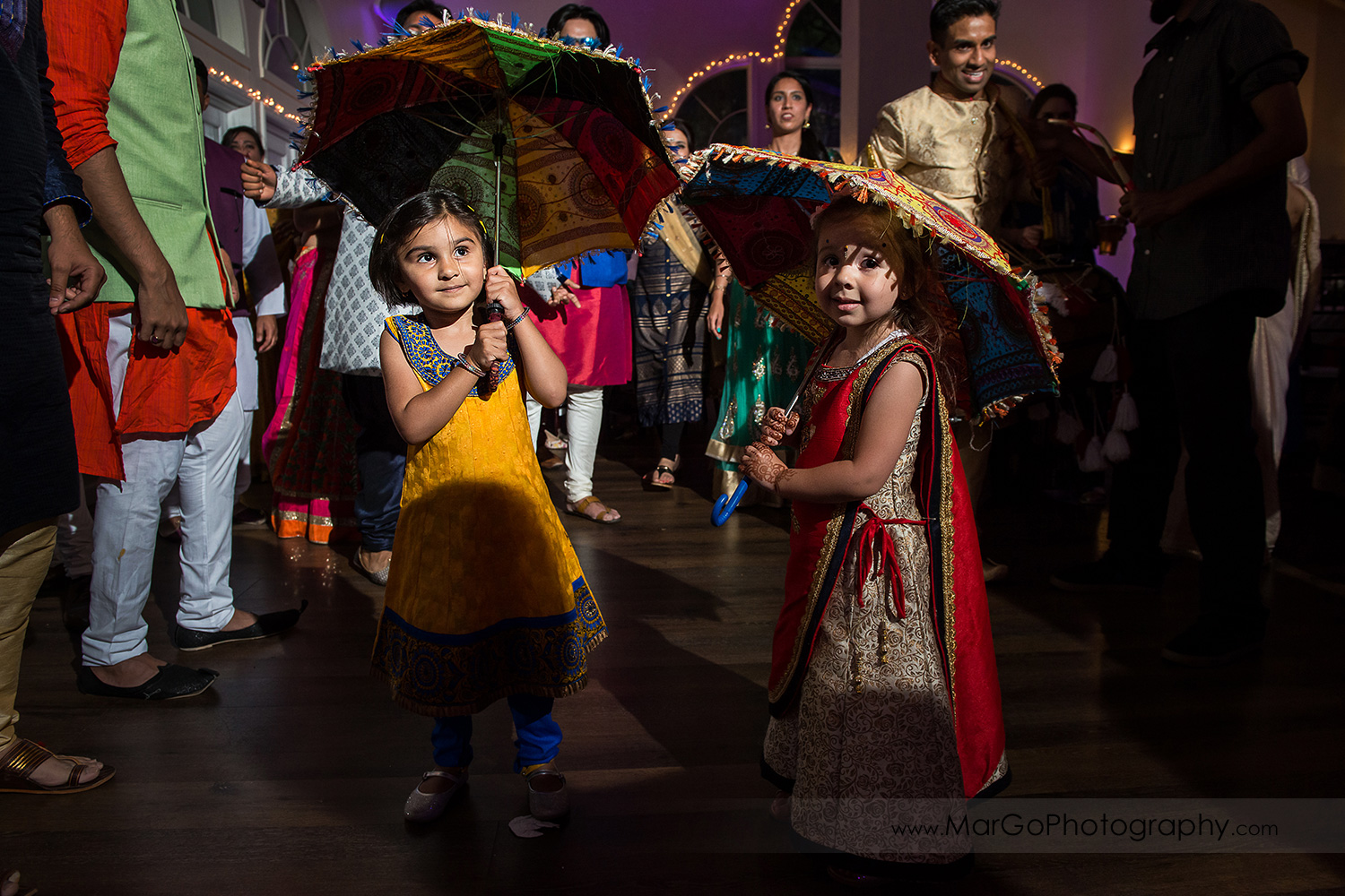 two little Indian girls under colorful umbrellas during wedding reception at Elliston Vineyards in Sunol