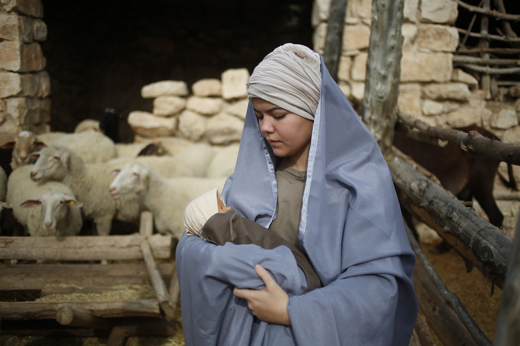 . A Christian actor portray Mary holds baby Jesus during a re-enactment of a Nativity scene during Christmas festivities at the Nazareth Village in Nazareth, northern Israel, Thursday, Dec. 21, 2017. (AP Photo/Ariel Schalit)