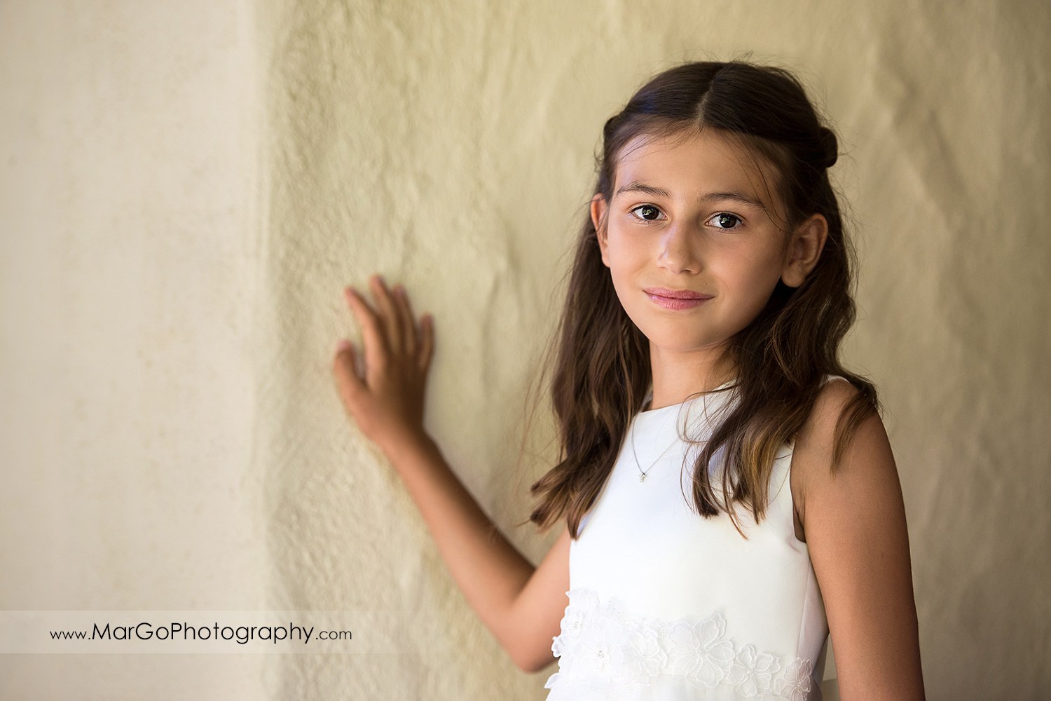 portrait of first communion girl in white dress on white wall at Cafe Wisteria in Menlo Park
