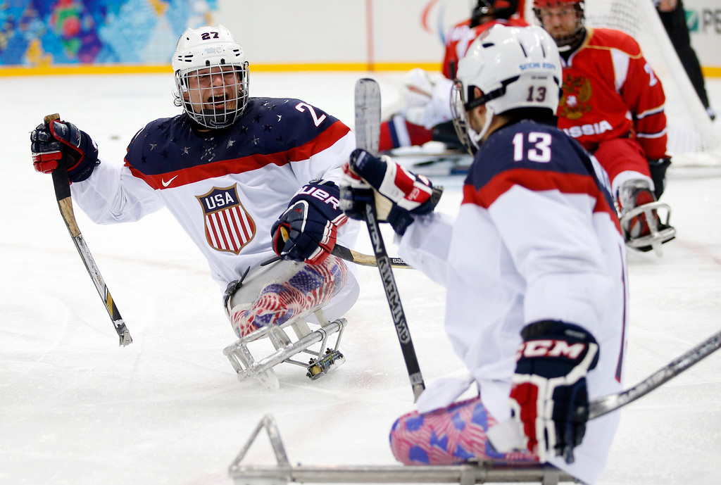 . United States\'s Joshua Pauls, left, celebrates as Joshua Sweeney, right scores a goal during the gold medal ice sledge hockey match between United States and Russia at the 2014 Winter Paralympics in Sochi, Russia, Saturday, March 15, 2014. (AP Photo/Pavel Golovkin)