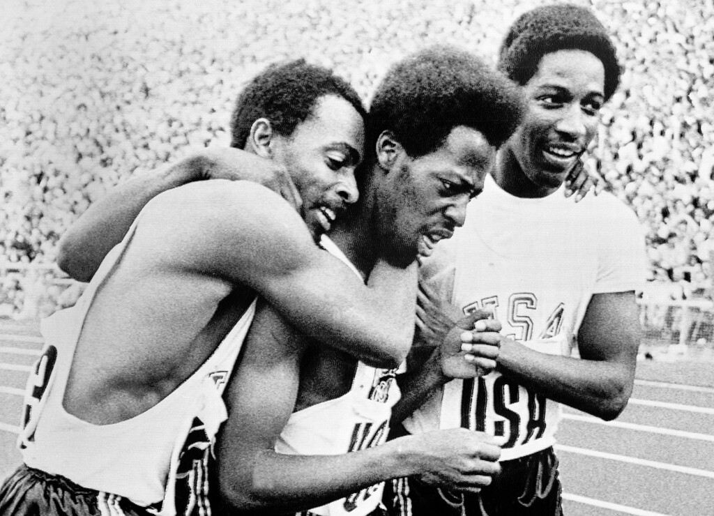 . Robert Taylor, left, of Houston, Texas, and Larry Black, right, of Miami, Fla., hug teammate Eddie Hart of Pittsburgh, Calif., after he ran last leg of relay to bring the Americans victory in the 400 meter relay event at the Munich Olympic stadium on Sept. 10, 1972. They and the relay team\'s fourth man, Gerald Tinker (hidden behind the other three), equaled the world record for the run in 38.19 seconds. (AP Photo/Olympic Picture Pool)