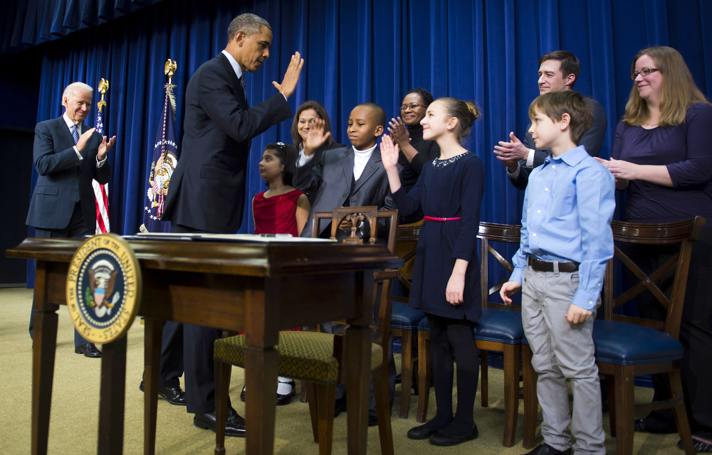 Description of . US President Barack Obama (2nd L) high-fives with children who wrote letters to his administration before signing executive orders during an event unveiling a package of proposals to reduce gun violence at the White House in Washington, DC, January 16, 2013. Obama signed 23 executive orders to curb gun violence and demanded Congress pass as assault weapons ban, in  a sweeping set of measures in response to the Newtown massacre.               AFP Photo/Jim  WATSON/AFP/Getty Images