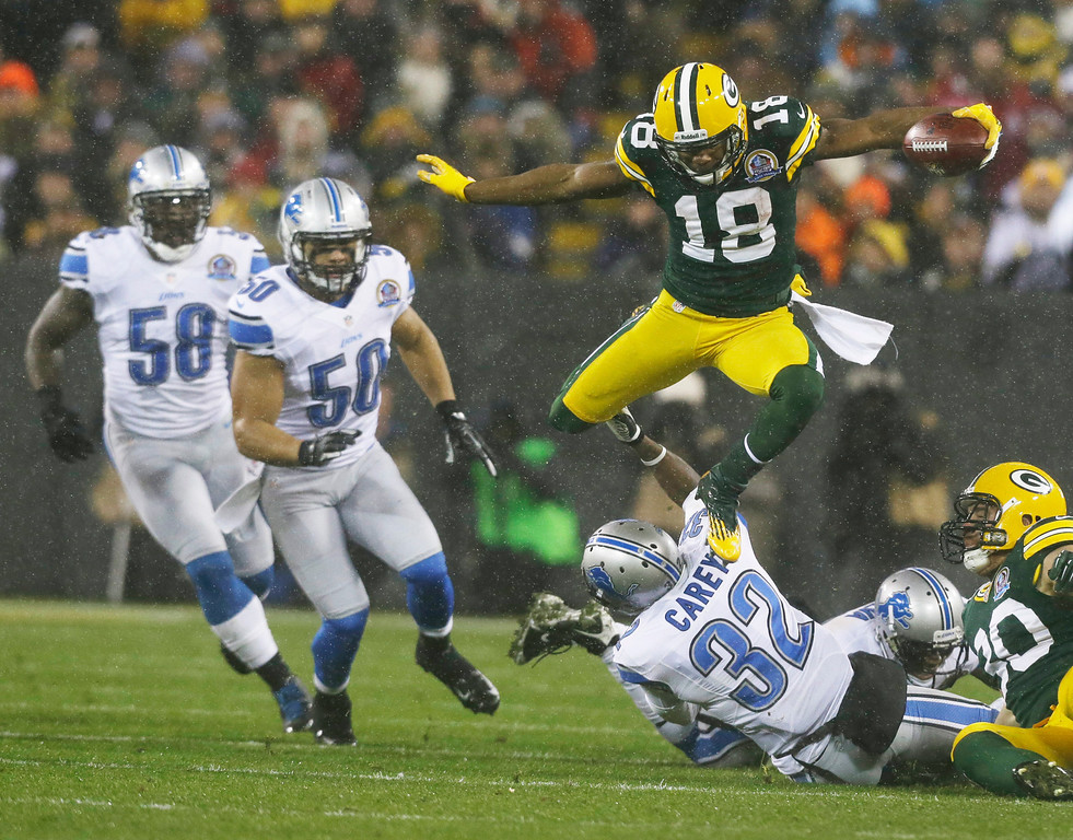 . Green Bay Packers\' Randall Cobb leaps over Detroit Lions\' Don Carey (32) as he runs back a kick during the first half of an NFL football game Sunday, Dec. 9, 2012, in Green Bay, Wis. (AP Photo/Jeffrey Phelps)
