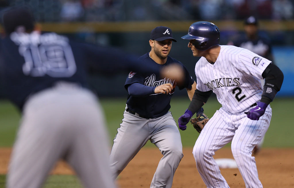 . Atlanta Braves second baseman Tommy La Stella, back left, tags out Colorado Rockies\' Troy Tulowtizki, back right, as he gets caught in a rundown between first and second bases after hitting a single in the fifth inning of a baseball game in Denver on Wednesday, June 11, 2014. (AP Photo/David Zalubowski)