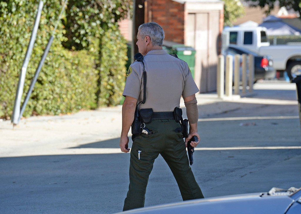 . A man in handcuffs eluded Sheriff\'s deputies before finally being caught hiding in a trash can in the alley behind the 700 block of 10th Street in San Pedro Wednesday, December 03, 2013.  A deputy scans the alley with gun drawn where the subject was found. Photo by Steve McCrank/DailyBreeze