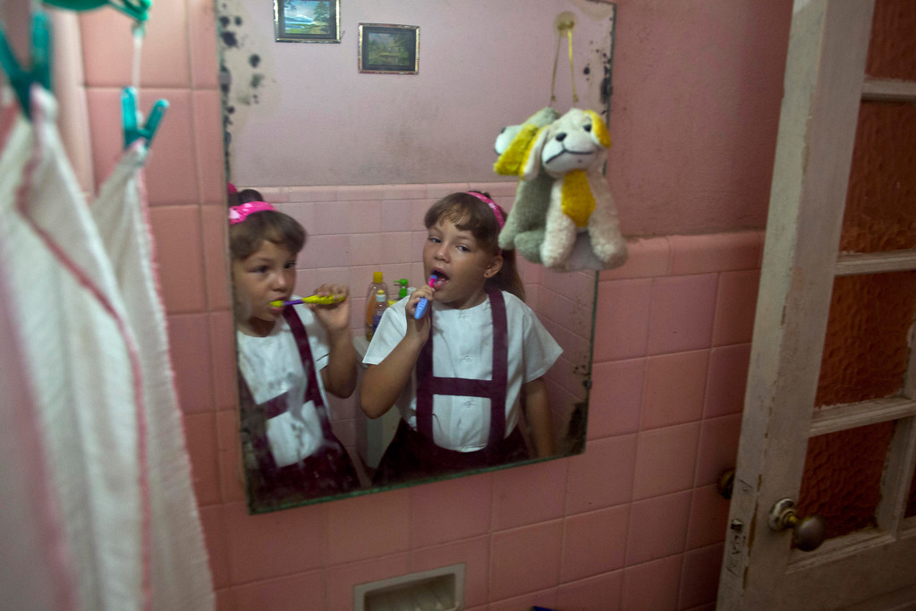 """. In this Sept. 23, 2013 photo, six-year-old twin sisters Asley and Aslen Velazquez prepare for school in Havana, Cuba. Their mother Tamara Velazquez said she never expected to have twins from her first pregnancy and did not take fertility treatments. \""""It\'s a lot of work. It requires a lot of patience,\"""" Velazquez said. \""""They are very active and dominant, although each has a different character.\""""  (AP Photo/Ramon Espinosa)"""