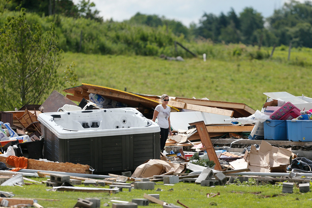 . A woman walks through debris of a destroyed house after Tuesday night\'s storm, on Wednesday, July 9, 2014, in Smithfield, N.Y.  (AP Photo/Mike Groll)