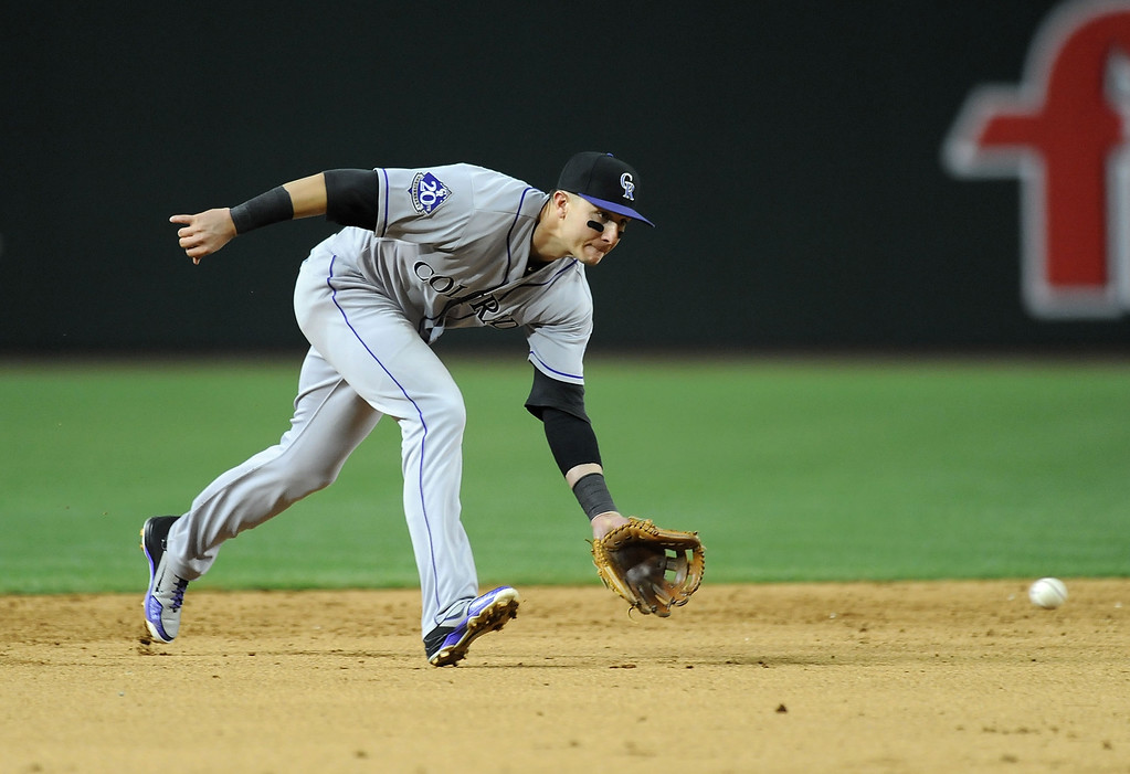 . PHOENIX, AZ - APRIL 25:  Troy Tulowitzki #2 of the Colorado Rockies makes a play on a ground ball against the Arizona Diamondbacks at Chase Field on April 25, 2013 in Phoenix, Arizona.  (Photo by Norm Hall/Getty Images)