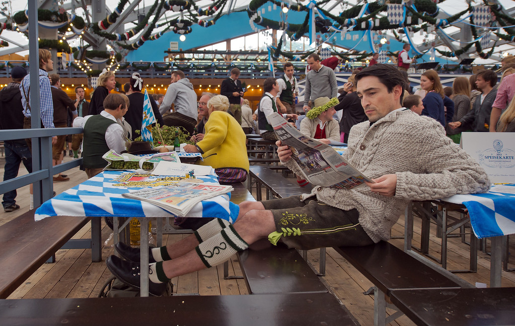 ". A Visitor in bavarian style clothes reads a newspaper after he has entered the ""Schottenhamel\"" beer tent as fast as possible to reserve places for friends for the official launch of the Oktoberfest 2013 beer festival at Theresienwiese on September 21, 2013 in Munich, Germany. Munichs mayor Christian Ude will launch the Oktoberfest at 12.00 o\'clock in the Schottenhamel-tent by tapping the first barrel of beer with the traditional \""O\'zapft is!\"" (\""It\'s tapped!\""). The Munich Oktoberfest, which this year will run from September 21 through October 6, is the world\'s largest beer fest and draws millions of visitors. (Photo by Joerg Koch/Getty Images)"