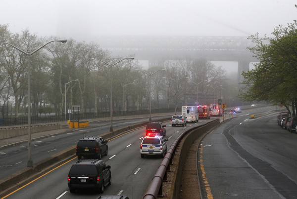 . Part of the Williamsburg Bridge peeks through thick morning fog as police and fire department vehicles lead a procession along Franklin D. Roosevelt East River Drive with the unidentified remains of victims of the Sept. 11, 2001 attacks as they are returned to the World Trade Center site, Saturday, May 10, 2014, in New York. The remains were moved from the Office of the Chief Medical Examiner on Manhattan\'s East Side at dawn Saturday to an underground repository in the same building as the National September 11 Memorial Museum. (AP Photo/Julio Cortez)