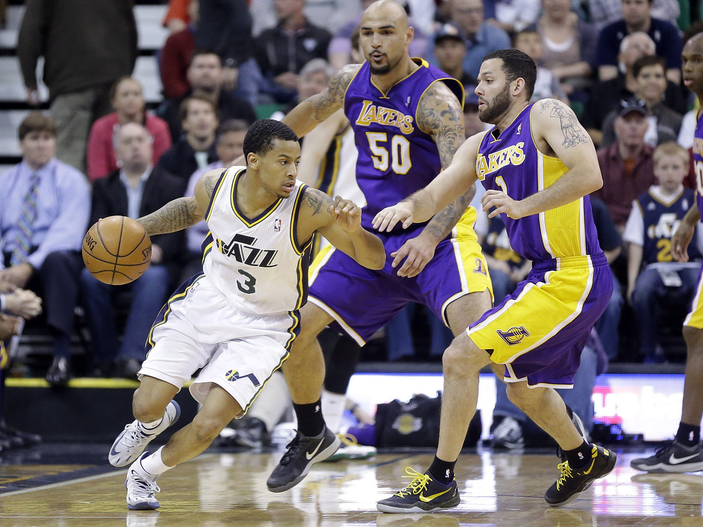 . Utah Jazz\'s Trey Burke (3) drives on Los Angeles Lakers\' Robert Sacre (50) and Jordan Farmar (1) in the second half during an NBA basketball game Monday, April 14, 2014, in Salt Lake City, Utah. (AP Photo/Rick Bowmer)