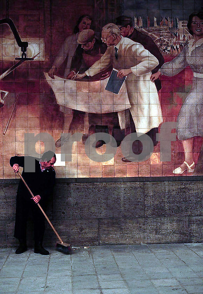 Man sweeping sidewalk by the city building where work permits are issued, Berlin, Germany.