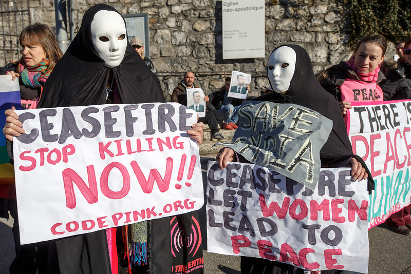 """. Masked members of the movement \""""Codepink women for peace\"""" protest near the hotel, during the opening of the Geneva II peace talks on Syria , in Montreux, Switzerland, Wednesday, January 22, 2014.   (AP Photo/Keystone,Salvatore Di Nolfi)"""