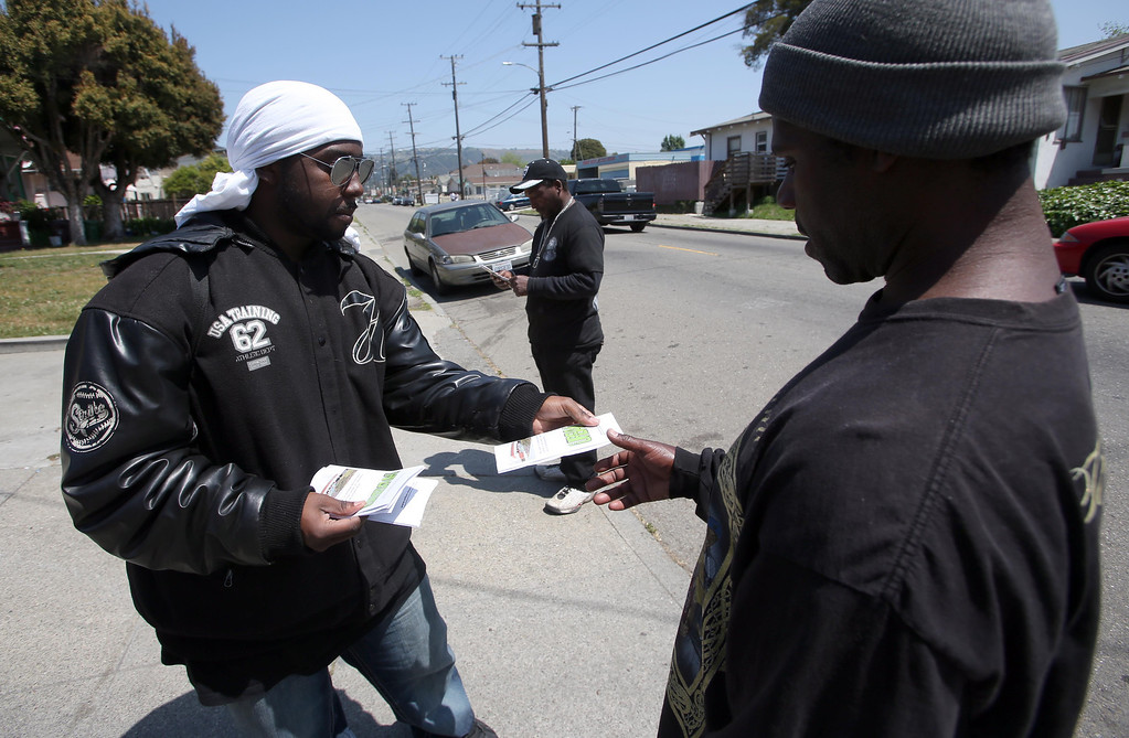 . Urban Church volunteer Jaron Isom, of Oakland, left, passes out flyers and neighborhood surveys along International Boulevard near Seminary Avenue in Oakland, Calif., on Friday, April 26, 2013.  They are working in hopes of helping to reduce the violence in the neighborhood. (Jane Tyska/Staff)