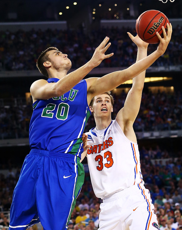 . ARLINGTON, TX - MARCH 29:  Chase Fieler #20 of the Florida Gulf Coast Eagles goes up against Erik Murphy #33 of the Florida Gators in the first half during the South Regional Semifinal round of the 2013 NCAA Men\'s Basketball Tournament at Dallas Cowboys Stadium on March 29, 2013 in Arlington, Texas.  (Photo by Ronald Martinez/Getty Images)