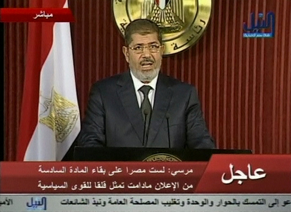Description of . Egyptian President Mohamed Mursi speaks during a televised address in Cairo, in this still image taken from video made available to Reuters on December 6, 2012. Mursi invited political groups, judges and others to meet on Saturday for a national dialogue on a political road map after a referendum on a new constitution, which he signalled would go ahead as scheduled on Dec. 15. REUTERS/Nile TV via Reuters TV