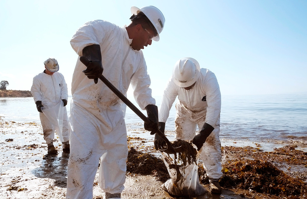 . Crews from Patriot Environmental Services collect oil-covered seaweed and sand from the shoreline at Refugio State Beach, north of Goleta, Calif., Wednesday, May 20, 2015.  A broken onshore pipeline spewed oil down a storm drain and into the ocean for several hours Tuesday before it was shut off, creating a slick some 4 miles long about 20 miles west of Santa Barbara.  (AP Photo/Michael A. Mariant)
