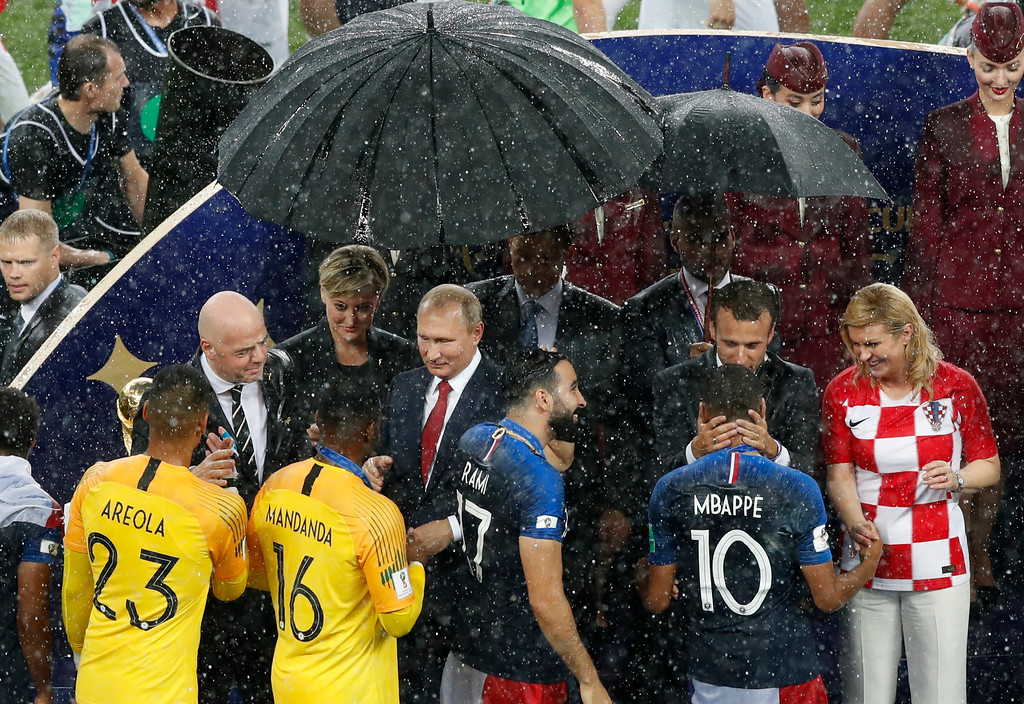 . FIFA President Gianni Infantino, Russian President Vladimir Putin, French President Emmanuel Macron and Croatian President Kolinda Grabar-Kitarovic, from left, congratulate French players on their victory as they are presented with medals after the final match between France and Croatia at the 2018 soccer World Cup in the Luzhniki Stadium in Moscow, Russia, Sunday, July 15, 2018. France won the final 4-2. (AP Photo/Rebecca Blackwell)