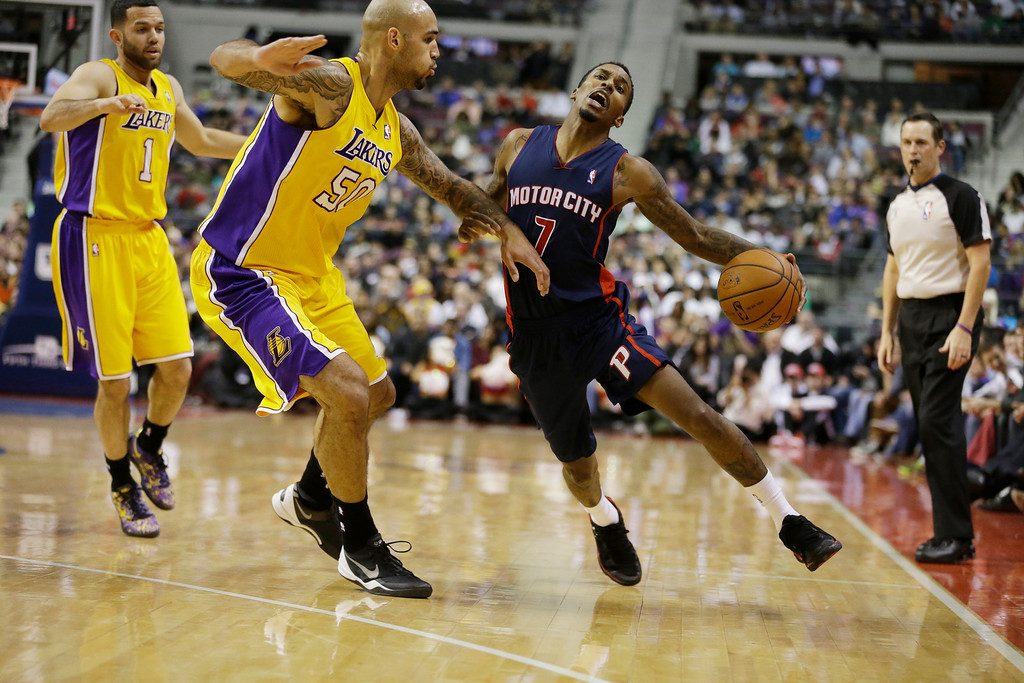 . Detroit Pistons guard Brandon Jennings (7) drives around Los Angeles Lakers center Robert Sacre (50) during the second half of an NBA basketball game at the Palace in Auburn Hills, Mich., Friday, Nov. 29, 2013. (AP Photo/Carlos Osorio)