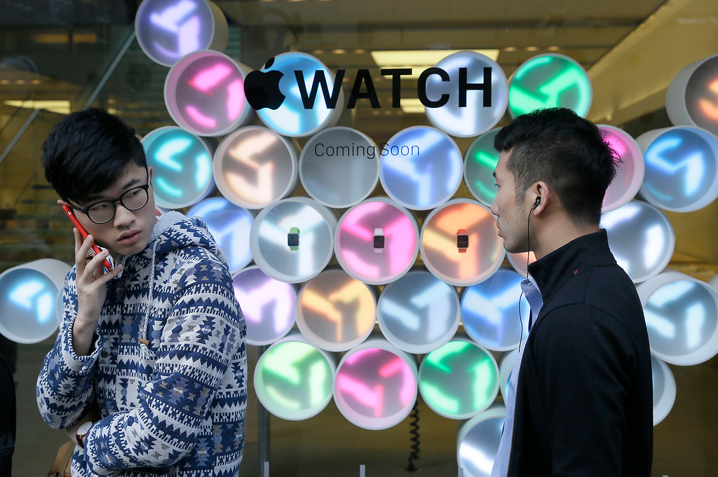 . Customers wait in line outside an Apple store in front of a display for Apple\'s new watch in San Francisco, Friday, April 10, 2015. Apple has started taking orders for the watch on its website and the Apple Store app. Currently, that\'s the only way Apple is selling the watch, with shipments scheduled to start April 24. (AP Photo/Eric Risberg)