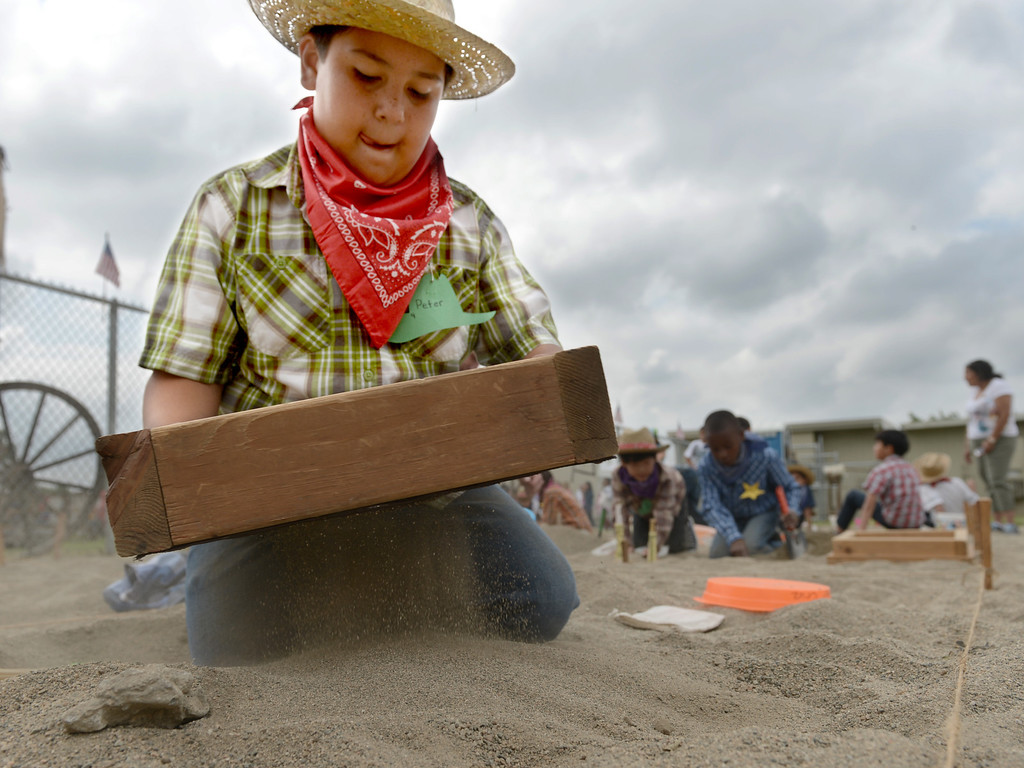 . Peter Cruz, 10, shifts through dirt as he pans for gold at the annual Gold Rush Day at Sierra Vista Elementary School in Upland May 17, 2013. About 60 students paned for gold while learned all about the Gold Rush at the school.  (Thomas R. Cordova/Staff Photographer)