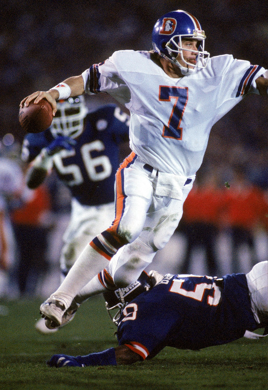 . Quarterback John Elway #7 of the Denver Broncos avoids a tackle by linebacker Carl Banks #58 of the New York Giants during Super Bowl XXI at the Rose Bowl on January 25, 1987 in Pasadena, California.  The Giants won 39-20.  (Photo by George Rose/Getty Images)