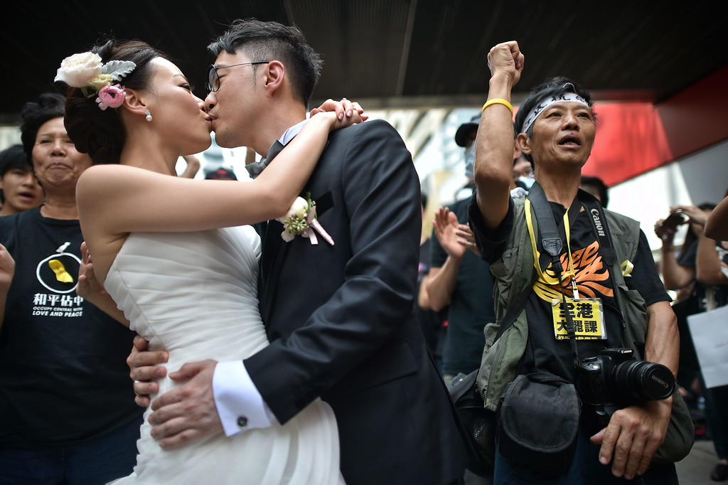 . A couple take wedding photogtaphs in front of pro-democracy protesters in Hong Kong on October 1, 2014. Hong Kong protesters who braved thunderstorms to stage their third night of pro-democracy rallies began massing on October 1 at the city\'s Golden Bauhinia Square as China\'s National Day holiday lent their campaign for free elections fresh momentum. PHILIPPE LOPEZ/AFP/Getty Images