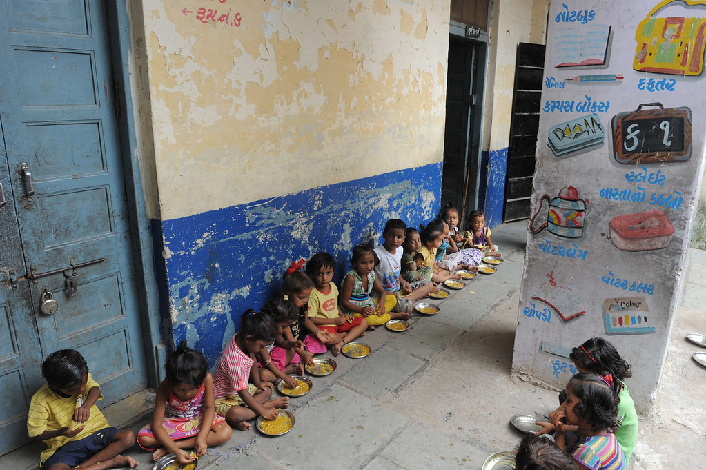 . Indian schoolchildren at Jahangirpura Shala Number 2, which is run by the Ahmedabad Municipal Corporation, eat their free mid-day meal in Ahmedabad on July 17, 2013. Twenty-two children have died in India\'s Bihar state after eating a free lunch feared to contain poisonous chemicals at an Indian primary school, officials said July 17, as the tragedy sparked angry street protests.  SAM PANTHAKY/AFP/Getty Images