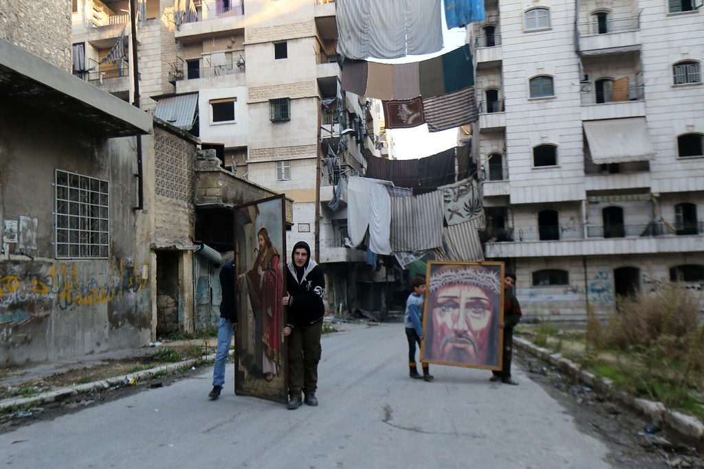 . Syrian youth carry religious paintings heading to a Catholic church before Christmas celebrations on December 24, 2014 in the rebel-held side of the northern city of Aleppo. Christians of various denominations make up around five percent of Syria\'s population.   ZEIN AL-RIFAI/AFP/Getty Images