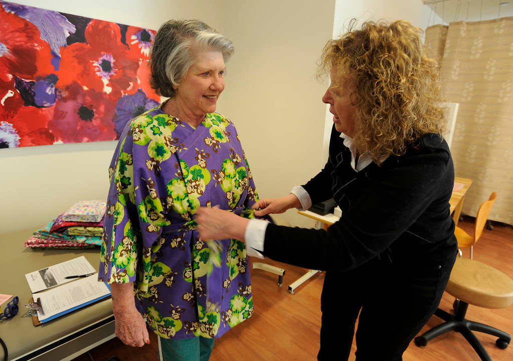 . (l-r) Joan Marlowe is outfitted with a Hug Wrap by Brenda Jones. Jones created her own open-in-the-front wrap when she was undergoing treatment for breast cancer, crafting an option to the hospital gown, utilizing soft and colorful flannel fabrics. Fellow patients loved them and her nonprofit Hug Wraps was born. Jones visited Providence Saint Joseph Medical Center�s Roy and Patricia Disney Family Cancer Center and gave patients free wraps. Burbank, CA 2/22/2013(John McCoy/Staff Photographer)