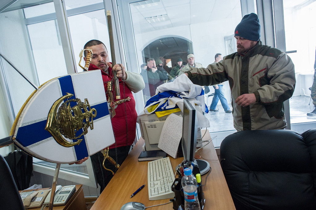 . Crimean  pro-Russian self-defense force members put down Ukrainian navy insignia after storming the Ukrainian navy headquarters in Sevastopol, Crimea, Wednesday, March 19, 2014. (AP Photo/Andrew Lubimov)