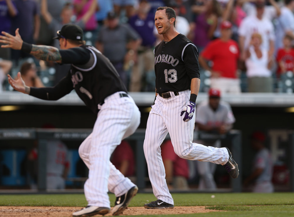 . Colorado Rockies\' Brandon Barnes, front, ushers teammate Drew Stubbs to home plate as Stubbs circles the bases after hitting a three-run, walkoff home run against the Cincinnati Reds in the ninth inning of the Rockies\' 10-9 victory in a baseball game in Denver on Sunday, Aug. 17, 2014. (AP Photo/David Zalubowski)